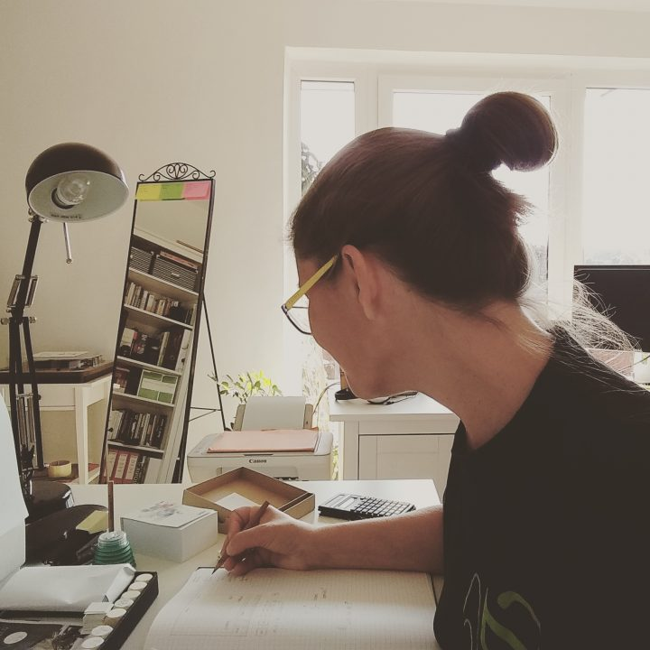 Elke am Schreibtisch, beim Zeichnen (Verpackungsdesign der Biognosis Toolbox)
