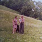 Meine Großeltern auf Heu-Wiese, mein Großvater hält mich am Arm (Kleinkind).