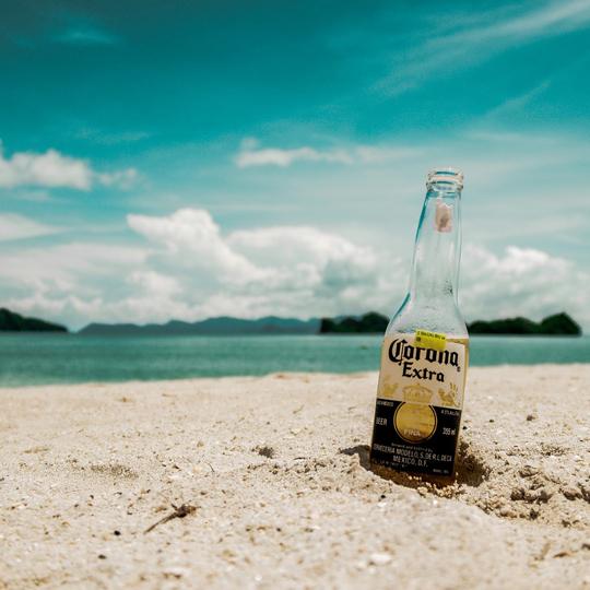 Corona Bierflasche am Strand, im Hintergrund Meer